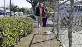 Residents walk through a muddy sidewalk in a flooded neighborhood Thursday, Feb. 23, 2017, in San Jose, Calif. Thousands of people evacuated from a flood in San Jose, California, returned home Thursday amid warnings to be careful about hygiene and handling food that may have come into contact with flood water. (AP Photo/Marcio Jose Sanchez)