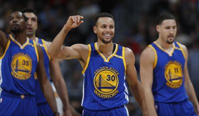 FILE - In this Nov. 10, 2016, file photo, Golden State Warriors guard Stephen Curry, center, jokes with teammates Kevin Durant, left, and Klay Thompson during the Warriors' NBA basketball game against the Nuggets in Denver. With all that was made before the season about adding Kevin Durant to an already star-studded roster, Golden State's players have jelled just fine. (AP Photo/David Zalubowski, File)