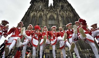 Male dancers perform in front of the world famous Cologne cathedral when tens of thousands revelers dressed in carnival costumes celebrate the start of the street-carnival in  Cologne, Germany, Thursday, Feb. 23, 2017. (AP Photo/Martin Meissner)
