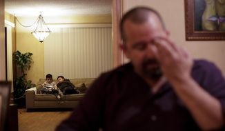 Mr. Lane, who did not give his first name, sits at the dining room table as his two children watch a movie in their home Wednesday, Feb. 22, 2017, in San Diego. The Lane family has been on edge since President Donald Trump took office. The mother, a Mexican who is in the country illegally, now carries her birth and marriage certificates and other documents wherever she goes. Around the country, Trump's efforts to crack down on the estimated 11 million immigrants living illegally in the U.S. have spread fear and anxiety and led many people to brace for arrest and to change up their daily routines in hopes of not getting caught. (AP Photo/Gregory Bull)