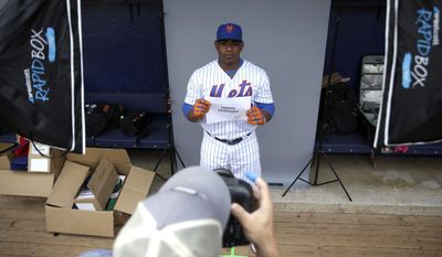 New York Mets left fielder Yoenis Cespedes poise for a photographer during picture day before a spring training baseball workout Wednesday, Feb. 22, 2017, in Port St. Lucie, Fla. (AP Photo/David J. Phillip)