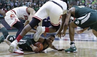 Michigan State guard Alvin Ellis III, on ground, controls the ball during the first half of the team's NCAA college basketball game against Nebraska, Thursday, Feb. 23, 2017, in East Lansing, Mich. (AP Photo/Carlos Osorio)