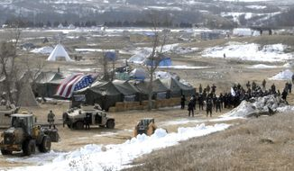 Law enforcement enters the Oceti Sakowin camp to begin arresting Dakota Access Pipeline protesters  in Morton County, Thursday, Feb. 23, 2017, near Cannon Ball, N.D. As the arrests were underway law enforcement personnel drove several large construction equipment into the camp to begin the cleanup process of razing tents and structures.  (Mike McCleary/The Bismarck Tribune via AP, Pool)