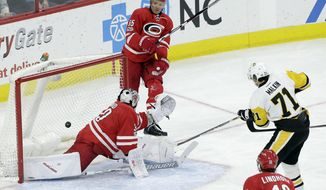 Pittsburgh Penguins' Evgeni Malkin (71), of Russia, scores against Carolina Hurricanes goalie Cam Ward as Hurricanes' Ron Hainsey (65) watches at rear during the third period of an NHL hockey game in Raleigh, N.C., Tuesday, Feb. 21, 2017. Pittsburgh won 3-1. (AP Photo/Gerry Broome)