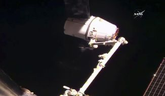 SpaceX's Dragon cargo ship is captured by astronauts at the International Space Station on Thursday, Feb. 23, 2017, a day after a GPS problem prevented the capsule from coming too close. (NASA TV via AP)