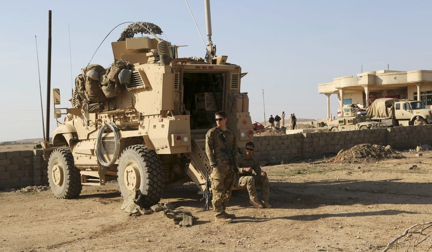 In this Thursday, Feb. 23, 2017 photo, U.S. Army soldiers stand outside their armored vehicle on a joint base with Iraqi army south of Mosul, Iraq. As Iraqi forces push into western Mosul coalition troops are closer to frontline fighting than ever before. Coalition forces have moved their bases closer to the front, relaxed their rules of engagement and during the push on Mosul airport coalition advisors were embedded with forward Iraqi rapid response and special forces units. Coalition officials say the change is helping speed up Iraqi military gains, but it marks a steady escalation of U.S. involvement in Iraq that could undermine the sustainability of Iraq's territorial victories. (AP Photo/ Khalid Mohammed)