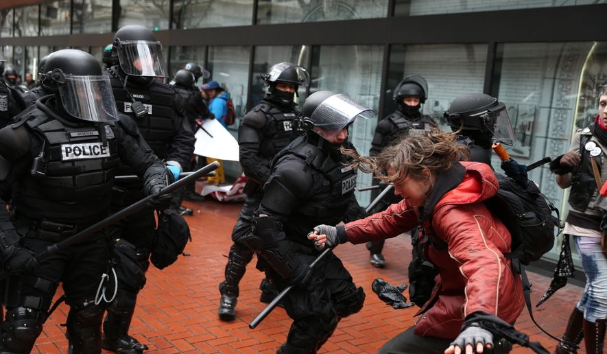 """Protesters clash with police in Portland, Ore., on Monday, Feb. 20, 2017. Thousands of demonstrators turned out Monday across the U.S. to challenge President Donald Trump in a Presidents Day protest dubbed """"Not My President's Day."""" (Dave Killen/The Oregonian via AP)"""