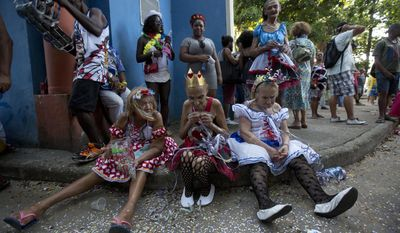 "Costumed patients from the Nise da Silveira Mental Health Institute wait for the start of their Carnival parade, coined in Portuguese: ""Loucura Suburbana,"" or Suburban Madness, in the streets of Rio de Janeiro, Brazil, Thursday, Feb. 23, 2017. Patients, their relatives and institute workers held their parade one day before the official start of Carnival. (AP Photo/Silvia Izquierdo)"