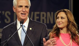 FILE- In this Nov. 4, 2014 file photo, Charlie Crist gestures as he stands with his wife Carole during speech in Tampa, Fla. After nine years of marriage, U.S Rep. Charlie Crist has filed for divorce. (AP Photo/Chris O'Meara, File)