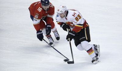 Florida Panthers center Aleksander Barkov (16) and Calgary Flames center Sam Bennett (93) go for the puck during the second period of an NHL hockey game, Friday, Feb. 24, 2017, in Sunrise, Fla. (AP Photo/Lynne Sladky)