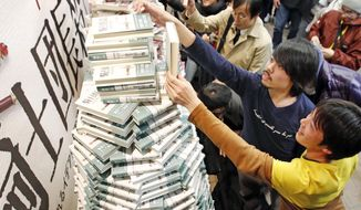 """People buy copies of the new book written by Haruki Murakami at a book store in Tokyo shortly after midnight, Friday, Feb. 24, 2017. Murakami's new book """"Kishidancho Goroshi,"""" or """"Killing Commendatore,"""" is a two-part story about a 36-year-old portrait painter and the mysterious incidents that happen after his wife divorces him and he moves into an old house on a mountainside west of Tokyo. (Fumine Tsutabayashi/Kyodo News)"""