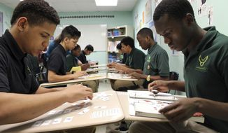 """In this Feb. 15, 2017, photo, Patient Inganya, right, and Enrique Veliz, left, do classwork at Phoenix Academy in Lancaster, Pa. The Lancaster community runs an """"international school"""" on its main high school campus to help the waves of new arrivals sponsored by local resettlement agencies learn English and adjust to American schools. But the practice of sending the ones who are over 16 and have no school records to Phoenix, an alternative school across town, has rattled critics who see it as a diploma mill. (AP Photo/Michael Rubinkam)"""