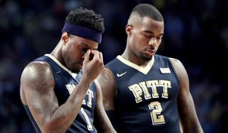 FILE - In this March 5, 2016, file photo, Pittsburgh's Jamel Artis, left, and teammate Michael Young walk on the court in the final seconds of a 63-59 loss to Georgia Tech, in an NCAA college basketball game in Atlanta. Artis and Young have spent the last four years enduring the ups and downs at Pittsburgh. The two friends and seniors will play their final home game at Petersen Events Center on Saturday against powerhouse North Carolina hoping to end a frustrating season on a high note.  (AP Photo/David Goldman, File)