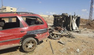 This image released by the Thiqa News Agency, damaged cars after a suicide attacker blew his small pick-up truck outside a security office in Sousian village, about 8 kilometers (5 miles) north of al-Bab, Friday, Feb. 24, 2017. A car bombing north of a Syrian town just captured by Turkish forces and Syrian opposition fighters from the Islamic State group killed several people, mostly civilians who had gathered trying to go back home, Turkey's news agency and Syrian activists said. (Thiqa News Agency, via AP)