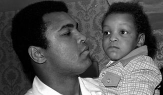 In this April 15, 1975 file photo, Heavyweight boxing champion Muhammad Ali, and Little Muhammad Ali, his 2 1/2 year old son, arrive at Miami Beach, Fla. Muhammad Ali's son, who bears the boxing great's name, was detained by immigration officials at a Florida airport and questioned about his ancestry and religion in what amounted to unconstitutional profiling, a family friend said Saturday, Feb. 25, 2017. (AP Photo/File)