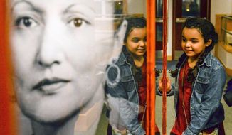 In this Thursday, Feb. 16, 2017 photo, Peri Blair looks at a new permanent exhibit honoring Tlingit civil rights activist Elizabeth Peratrovich in Ketchikan, Alaska, following the unveiling of the exhibit and the naming of the Elizabeth Peratrovich Theater in the Southeast Alaska Discovery Center. Peratrovich, born in Petersburg in 1911 as a Tlingit of the Raven-Sockeye clan, is celebrated for her role in the passage of the Anti-Discrimination Act of 1945, one of the first of its kind in the United States, in territorial Alaska. (Taylor Balkom/Ketchikan Daily News via AP)
