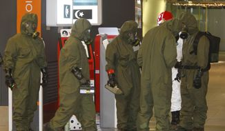 Hazmat crews gather at the main hall of Kuala Lumpur International Airport 2 in Sepang, Malaysia on Sunday, Feb. 26, 2017. Malaysian police order a sweep of Kuala Lumpur airport for toxic chemicals and other hazardous substances following the killing of Kim Jong Nam. (AP Photo/Daniel Chan)