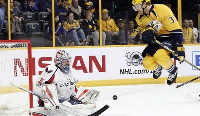 Nashville Predators left wing Colin Wilson (33) jumps out of the way of a shot against Washington Capitals goalie Philipp Grubauer (31), of Germany, during the second period of an NHL hockey game Saturday, Feb. 25, 2017, in Nashville, Tenn. (AP Photo/Mark Humphrey)