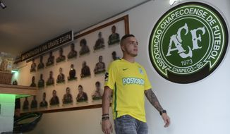 In this Feb. 18, 2017 photo, Juan David Pemberty walks out of bar Chapecoense, which he opened with his wife in honor of the Brazilian soccer team Chapecoense, in Medellin, Colombia. All but three of the players photos are in somber black and white, honoring players who died when a charter plane went down near Medellin on Nov. 28, 2016 wiping out nearly the entire Chapecoense team from Brazil. (AP Photo/Luis Benavides)