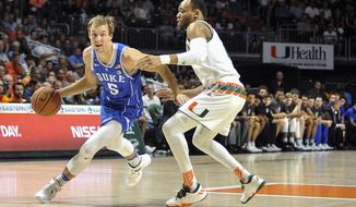 Duke guard Luke Kennard, left,attempts to drive past Miami guard Bruce Brown during first-half action in an NCAA college basketball game in Coral Gables, Fla., Saturday, Feb. 25, 2017. (AP Photo/Gaston De Cardenas)