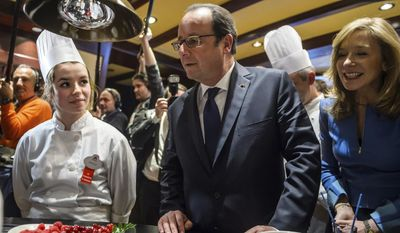 French President Francois Hollande, center, and Catherine Powell, right, president of Euro Disney watch apprentice cooks working as they attend a ceremony to mark the 25th anniversary of Disney Land in Marne-la-Vallee, north of Paris, Saturday Feb. 25, 2017. Hollande visited Disneyland Paris as Europe's most popular tourist attraction struggles with long-running financial challenges. (Christophe Petit Tesson/Pool photo via AP)