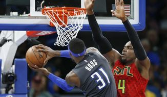 Orlando Magic forward Terrence Ross (31) shoots around Atlanta Hawks forward Paul Millsap (4) during the second quarter of an NBA basketball game in Orlando, Fla., on Saturday, Feb. 25, 2017. (AP Photo/Reinhold Matay)