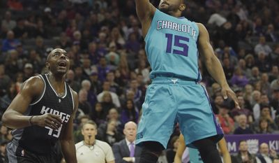 Charlotte Hornets guard Kemba Walker, right, goes to the basket as Sacramento Kings forward Anthony Tolliver, left, looks on during the first half of an NBA basketball game Saturday, Feb. 25, 2017, in Sacramento, Calif. (AP Photo/Rich Pedroncelli)
