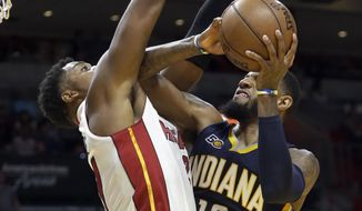 Indiana Pacers forward Paul George (13) goes to the basket as Miami Heat center Hassan Whiteside (21) defends during the first half of an NBA basketball game, Saturday, Feb. 25, 2017, in Miami. (AP Photo/Alan Diaz)