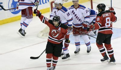New Jersey Devils' Adam Henrique (14) celebrates his goal as New York Rangers' Marc Staal (18) and Oscar Lindberg (24) look on during the second period of an NHL hockey game Saturday, Feb. 25, 2017, in Newark, N.J. (AP Photo/Bill Kostroun)