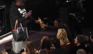 """Mahershala Ali, right, hands his award for best actor in a supporting role for """"Moonlight"""" to a tourist named Gary during the Oscars on Sunday, Feb. 26, 2017, at the Dolby Theatre in Los Angeles. (Photo by Chris Pizzello/Invision/AP)"""