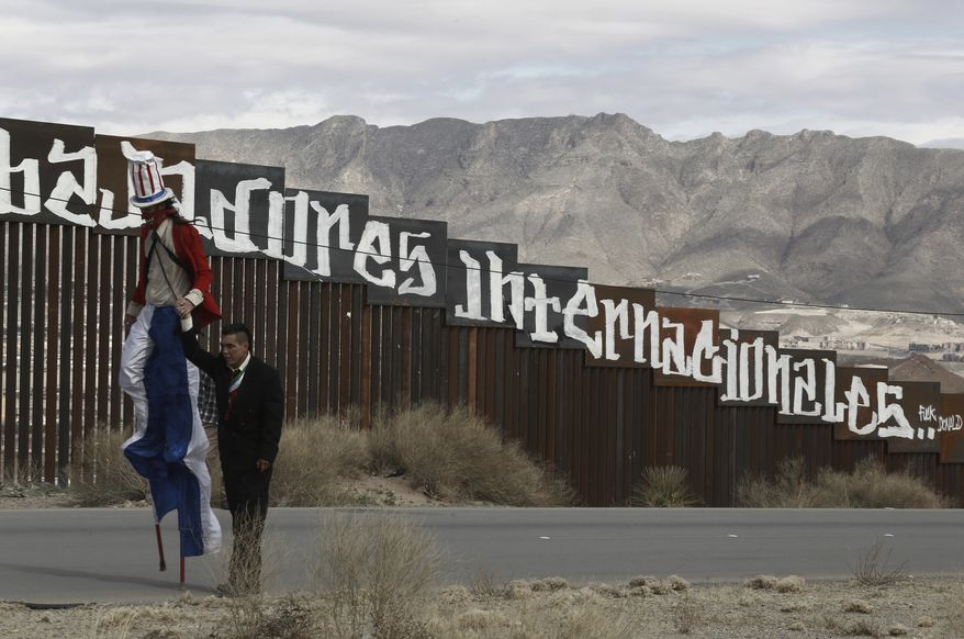 "Protestors dressed as a diabolical Uncle Sam, on stilts, and Mexico's President Enrique Pena Nieto hold hands as they walk along the border fence in Ciudad Juarez, Mexico Sunday, Feb. 26, 2017. A group of about 30 protestors gathered to paint slogans on the border wall and stage a performance mocking the relationship between Pena and President Donald Trump. The partial message in Spanish behind reads: ""Neither delinquents nor illegals, we are international workers."" (AP Photo/Christian Torres)"