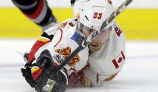 Calgary Flames' Sam Bennett (93) dives for the puck during the first period of an NHL hockey game against the Carolina Hurricanes in Raleigh, N.C., Sunday, Feb. 26, 2017. (AP Photo/Gerry Broome)