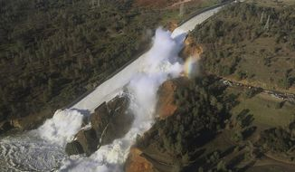 FILE - This Saturday, Feb. 11, 2017, file aerial photo released by the California Department of Water Resources shows the damaged spillway with eroded hillside in Oroville, Calif. California water authorities will cut the outflow from the dam to allow workers to remove debris piled at the base of its main spillway. The Department of Water Resources said Sunday, Feb. 26, 2017 it will start gradually reducing outflows from the Oroville Dam in Northern California starting Monday morning and completely stop them by the afternoon. (William Croyle/California Department of Water Resources via AP, File)