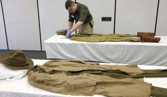 In this Feb. 13, 2017 photo, Nick Erickson works on outfitting a WWI uniform at the Grout Museum as part of the upcoming World War I in Waterloo, Iowa. The Grout Museum District is preparing for a centennial exhibition of the many uniforms and artifacts it has collected over the past several decades from families of local residents. (Matthew Putney/Waterloo Courier via AP)