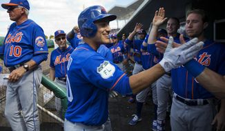 New York Mets' Michael Conforto, center, high-fives teammates after hitting a home run in the third inning of an exhibition spring training baseball game against the Boston Red Sox in Fort Myers, Fla., Friday, Feb. 24, 2017. (AP Photo/David Goldman)