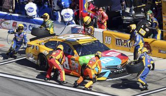 Crew members perform a pit stop on Kyle Busch's car during the NASCAR Daytona 500 auto race at Daytona International Speedway in Daytona Beach, Fla., Sunday, Feb. 26, 2017. (AP Photo/David Graham)