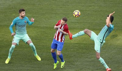 Atletico de Madrid's Kevin Gameiro, center, duels for the ball with Barcelona's Gerard Pique, left, and Sergio Busquets, right during a Spain's La Liga soccer match between Atletico de Madrid and FC Barcelona at the Vicente Calderon stadium in Madrid, Spain, Sunday, Feb. 26, 2017. (AP Photo/Daniel Ochoa de Olza)