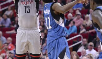 Houston Rockets guard James Harden (13) shoots a 3-pointer in front of Minnesota Timberwolves forward Andrew Wiggins (22) during the second half of an NBA basketball game Saturday, Feb. 25, 2017, in Houston. (AP Photo/George Bridges)
