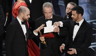 """La La Land"" producer Jordan Horowitz, left, presenter Warren Beatty, center, and host Jimmy Kimmel right, look at an envelope announcing ""Moonlight"" as best picture at the Oscars on Sunday, Feb. 26, 2017, at the Dolby Theatre in Los Angeles. It was originally announced mistakenly that ""La La Land"" was the winner. (Photo by Chris Pizzello/Invision/AP)"