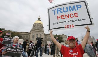 """Joe Webb, right, from Marietta, Ga., holds a sign in support of President Donald Trump. Backers of Pres. Trump gathered at the Georgia Capitol in Atlanta, Monday, Feb. 27, 2017, for a """"Spirit of America"""" rally to show their support for his agenda and push back against the wave of anti-Trump protests. (Bob Andres/Atlanta Journal-Constitution via AP)"""