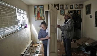 Julia Caudillo, left, cleans her flooded apartment with the help of friend Alberto Ramino, Monday, Feb. 27, 2017, in San Jose, Calif. Residents returned to a San Jose neighborhood after it was flooded by the nearby Coyote Creek following a series of storms last week. (AP Photo/Marcio Jose Sanchez)