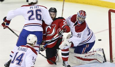 New Jersey Devils right wing Kyle Palmieri (21)takes a hard hit as he is squeezed between Montreal Canadiens defenseman Jeff Petry (26) and goalie Al Montoya (35) during the first period of an NHL hockey game, Monday, Feb. 27, 2017, in Newark, N.J. (AP Photo/Mel Evans)