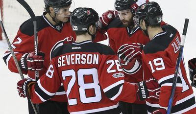 New Jersey Devils right wing Kyle Palmieri (21) celebrates his goal with teammates center Travis Zajac (19) defenseman Damon Severson (28) and defenseman John Moore (2) during the first period of an NHL hockey game against the Montreal Canadiens, Monday, Feb. 27, 2017, in Newark, N.J. (AP Photo/Mel Evans)