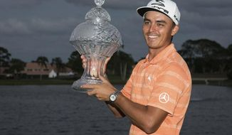 Golfer Rickie Fowler holds up the Honda Classic trophy after the conclusion of the golf tournament in Palm Beach Gardens, Fla., on Sunday, Feb. 26, 2017. (Michael Ares /The Palm Beach Post via AP)