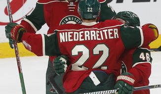 New Minnesota Wild player Ryan White, top, skates in to celebrate a goal by Nino Niederreiter of Switzerland off Los Angeles Kings goalie Jonathan Quick in the first period of an NHL hockey game Monday, Feb. 27, 2017, in St. Paul, Minn. White, obtained in a trade with the Coyotes, got an assist on the goal. (AP Photo/Jim Mone)