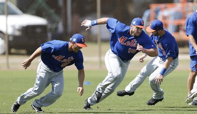 Former NFL quarterback and New York Mets outfielder Tim Tebow (15), center, works during a spring training baseball practice Monday, Feb. 27, 2017, in Port St. Lucie, Fla. (AP Photo/John Bazemore)