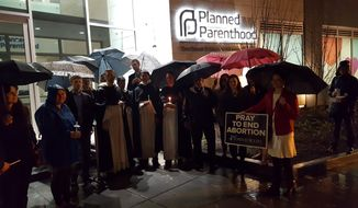 Two dozen pro-life activists maintained a vigil in the rain outside of a Planned Parenthood facility in the District Tuesday, the first day of a planned national 40 Days for Life annual campaign during Lent, which will see activists stationed outside abortion clinics nationwide from now until Easter weekend. (Bradford Richardson/The Washington Times)