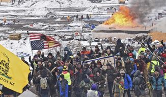 FILE - In this Feb. 22, 2017, file photo, a fire set by protesters burns in the background as opponents of the Dakota Access pipeline leave their main protest camp Wednesday near Cannon Ball, N.D. A federal judge will hear arguments Tuesday, Feb. 28, 2017, about whether to stop the final bit of construction on the disputed Dakota Access pipeline, perhaps just days before it could start moving oil.(Tom Stromme/The Bismarck Tribune via AP, File)