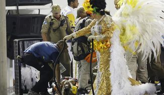 An injured person lies on a stretcher on the top of a float as she is being rescued during the performing of the Unidos da Tijuca samba school for the Carnival celebrations at the Sambadrome in Rio de Janeiro, Brazil, Tuesday, Feb. 28, 2017. Part of a float has collapsed during Rio de Janeiro's world famous Carnival parade, injuring several people, according to doctors at the scene. (AP Photo/Leo Correa)