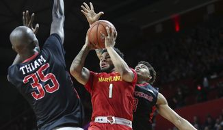 Maryland guard Jaylen Brantley (1) shoots as he splits Rutger guard Corey Sanders (3) and forward Issa Thiam (35) during the first half of an NCAA college basketball game Tuesday, Feb. 28, 2017, in Piscataway, N.J. (AP Photo/Mel Evans)